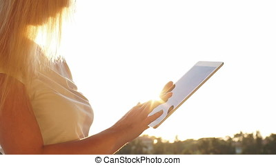 Woman uses digital tablet on the sunset. Slow Motion
