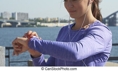 Woman uses her watches at the riverwalk - Macro shot of the...