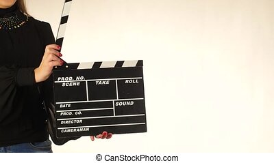 Woman uses movie clapper board, on white