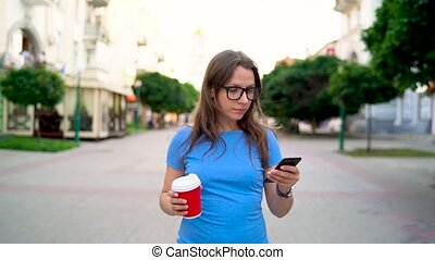 Woman uses smartphone and drinking coffee walking down the street. Slow motion