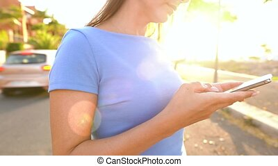 Woman uses smartphone on a palm street at sunset