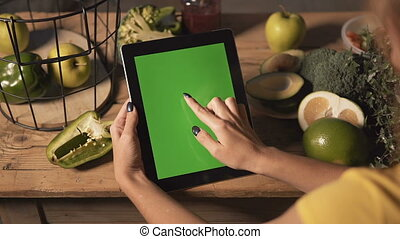 Woman Uses Tablet at Kitchen Table