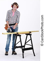 Woman using a circular saw to cut a wooden plank