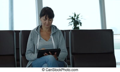 Woman using a digital tablet in airport waiting area