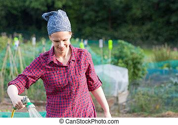 Woman using a garden hose nozzel