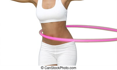 Woman using a hula hoop in her training against a white...