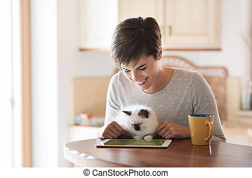 Woman using a laptop and cuddling her cat