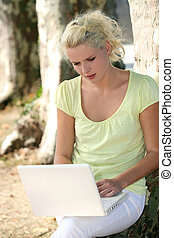 Woman using a laptop by a tree