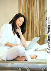 Woman using a laptop in her bedroom