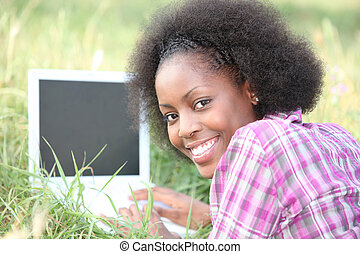 Woman using a laptop in the grass