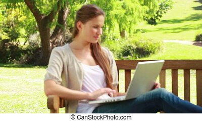 Woman using a laptop on a bench