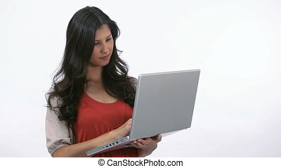 Woman using a laptop while holding