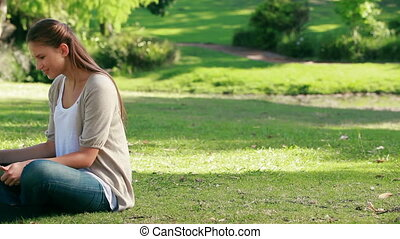 Woman using a laptop while sitting in a park