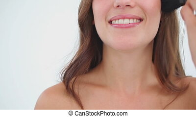 Woman using a make-up brush while smiling