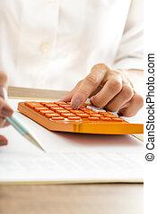 Woman using a manual calculator