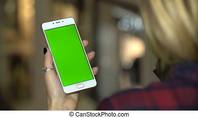 Woman using a mobile phone in mall with green screen, touch and scroll