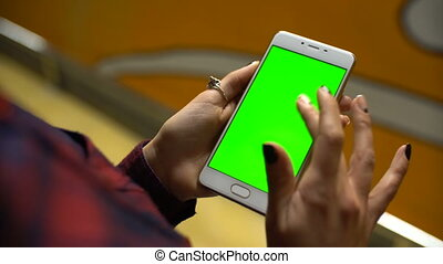 Woman using a mobile phone with green screen, touch and scroll