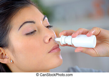 Woman using a nasal spray