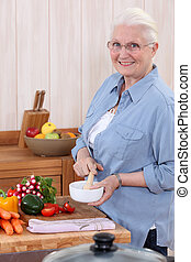 Woman using a pestle and mortar in the kitchen