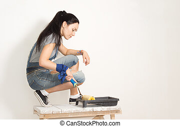 Woman using a roller to paint a wall