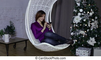 Woman using a smart phone, christmas background