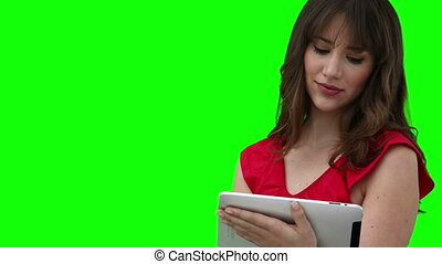 Woman using a tablet computer against a green background