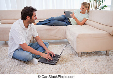 Woman using a tablet computer while her fiance is using a...