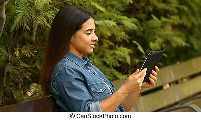 Woman using a tablet in a park - Happy woman using a tablet...