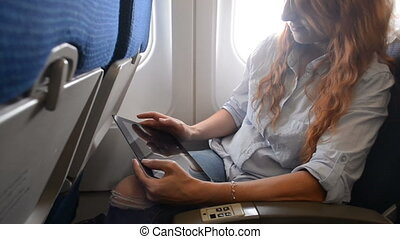 Woman using a tablet on an airplane