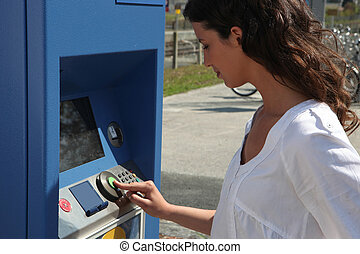 Woman using a ticket machine