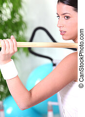 Woman using a wooden pole in the gym