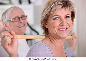 Woman using a wooden stick in a gym