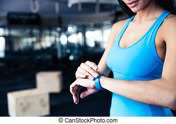 Woman using activity tracker at gym