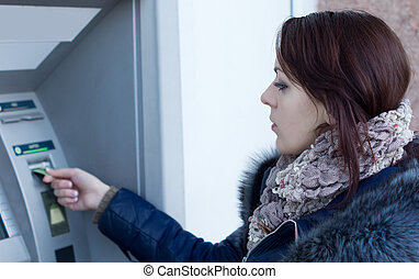 Woman using an Automated Teller machine at a bank inserting...