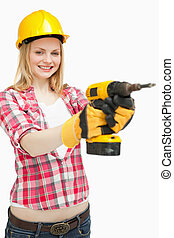 Woman using an electric screwdriver while smiling