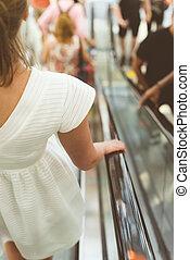 Woman using an escalator in metro.