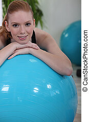 Woman using an exercise ball in a gym
