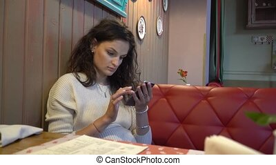 Woman using app on smartphone in cafe