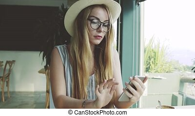 Woman using app on smartphone in cafe drinking coffee and smiling. Beautiful young girl texting on mobile phone.