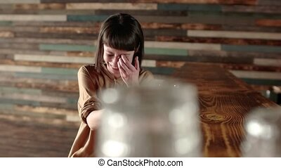 Woman using app on smartphone in cafe happy facial...