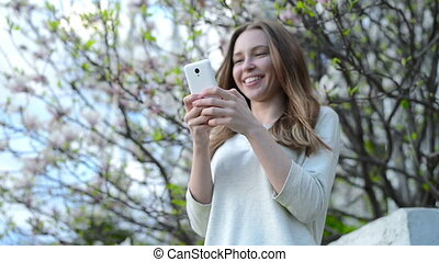 Woman using app on smartphone smiling and texting on mobile phone