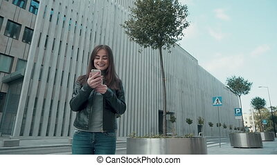 Woman Using App on Smartphone Smiling and Texting - Woman...