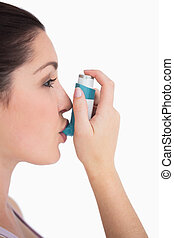 Woman using asthma inhaler against white background