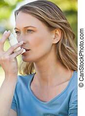 Woman using asthma inhaler in the park - Close-up of a young...