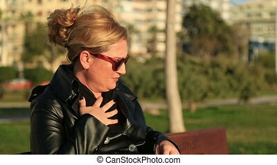 Woman using asthma inhaler - Woman seated on a park bench...