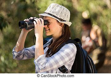 woman using binoculars bird watching