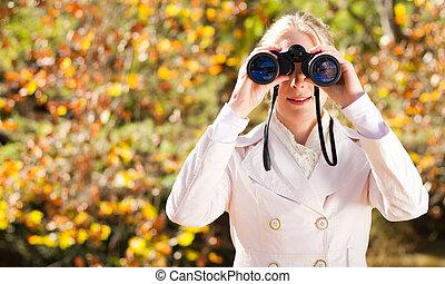 woman using binoculars in forest