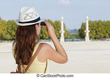 woman using binoculars on a city