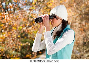 woman using binoculars outdoors