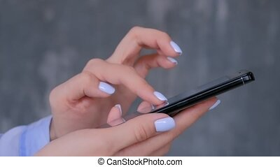 Woman using black smartphone with touchscreen display - close up side view